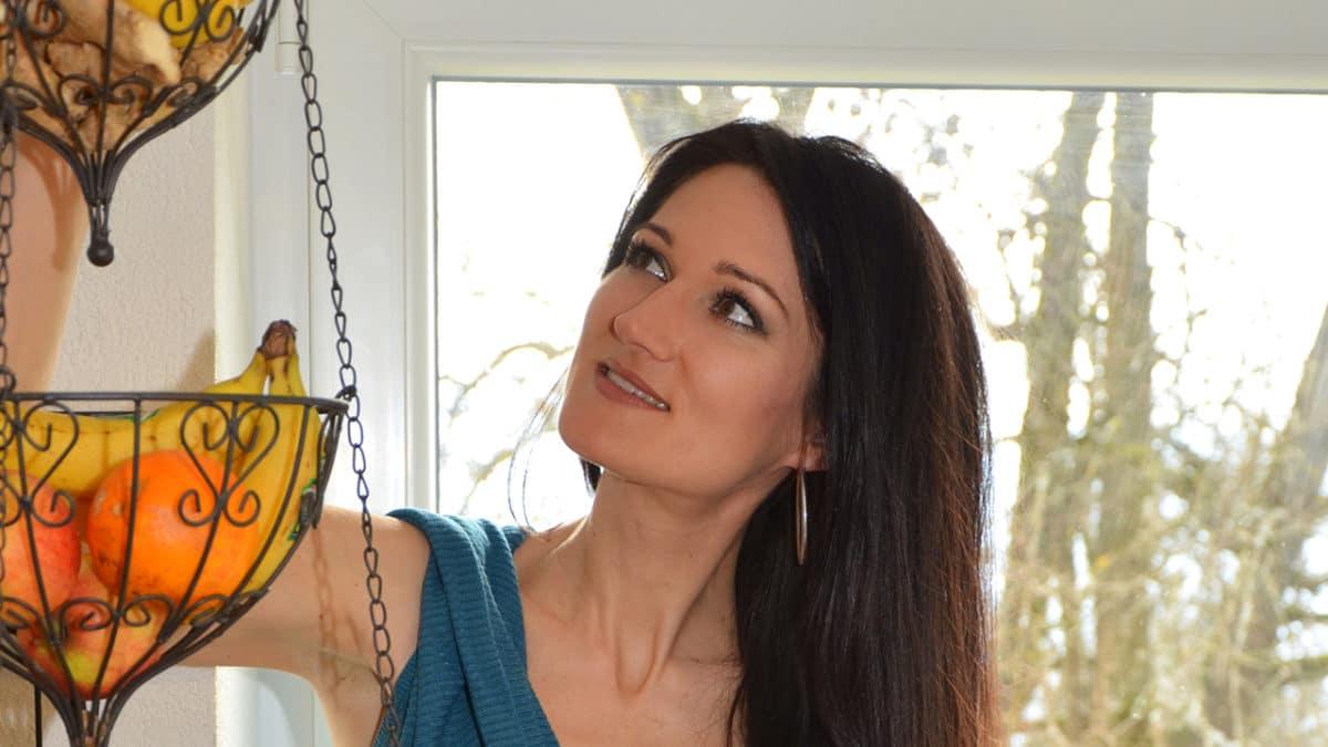Sandra Exl schaut in einen Korb voller basischer Früchte, die man beim Basenfasten essen darf.