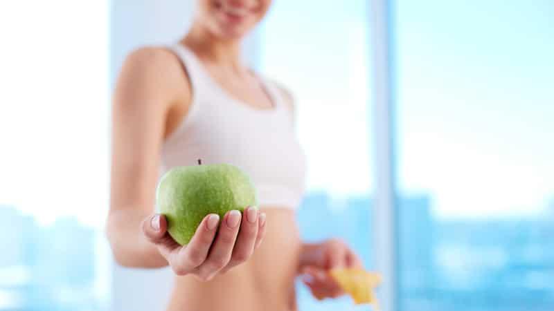 Eine Frau mit einem Apfel beim Fastenbrechen