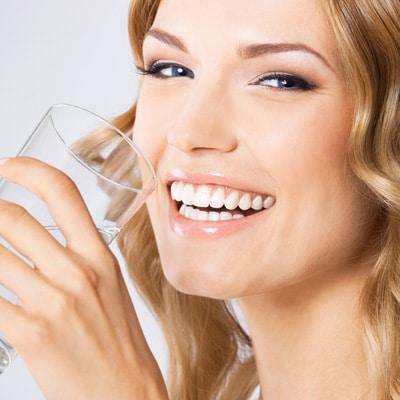 Eine hübsche Frau, die beim Heilfasten Wasser trinkt