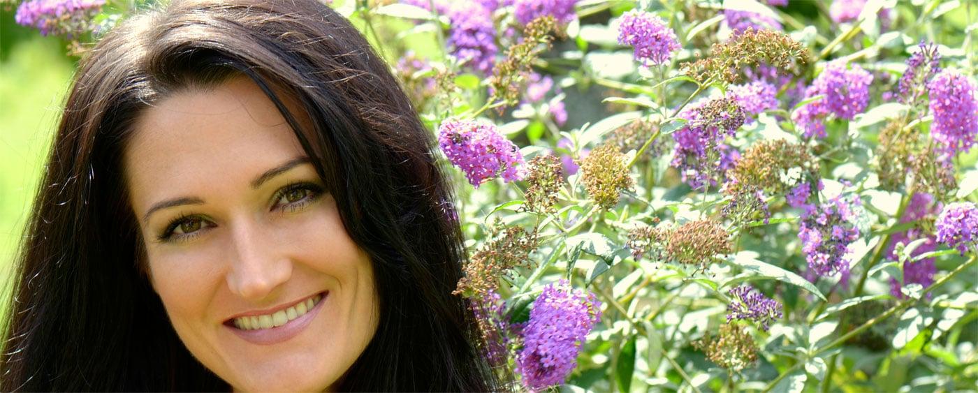 Sandra Exl vor einem Sommerflieder in Blüte