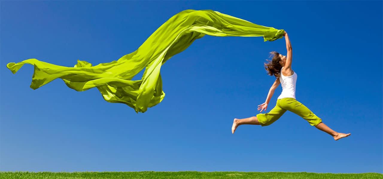 Eine Frau, die in die Luft springt, sie ist fröhlich und leicht. Ein Sujetbild für das Gefühl des Heilfastens, Entgiftens und Entschlackens