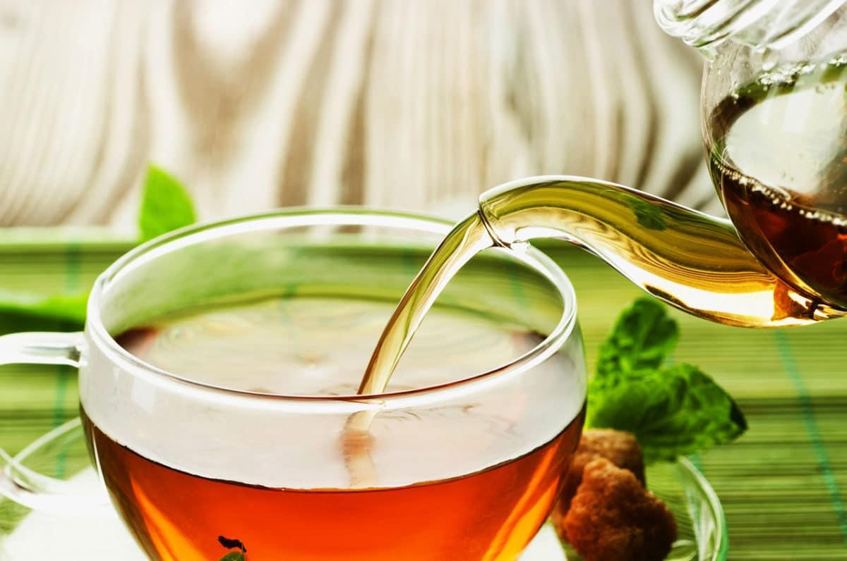 Eine durchsichtige Tasse Tee, die aus einer Teekanne befüllt wird