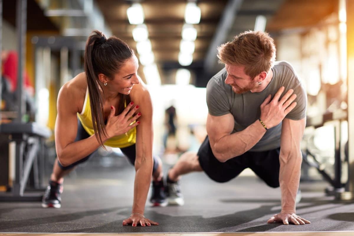 Zwei Leistungssportler bei ihren Übungen. Sie machen Liegestütz