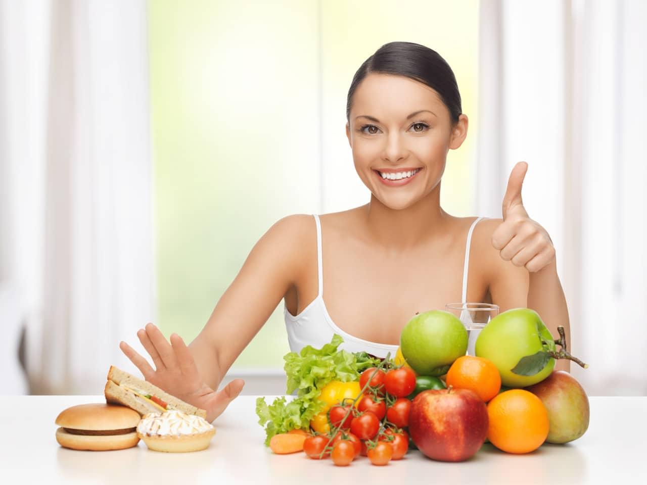 Eine Frau greift zu Gemüse und nicht Junkfood