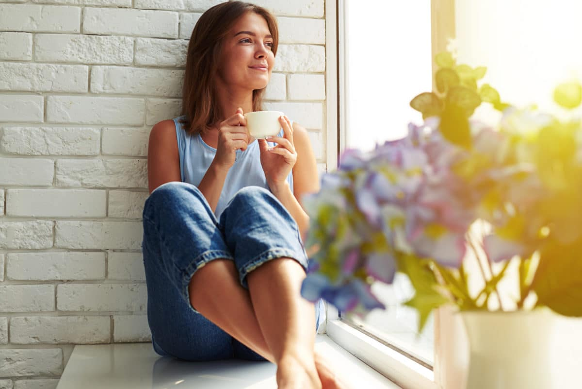 Eine Frau mit einem Fastentee auf einer Fensterbank